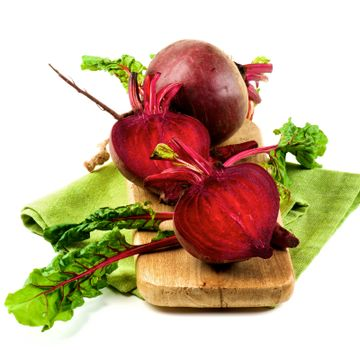One Full Body Fresh Raw Organic Beet Two Halves with Green Beet Tops on Wooden Board and Napkin isolated on White background