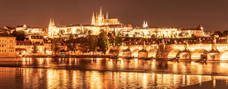 Golden Prague by night. Prague Castle and Charles Bridge reflected in Vltava River. View from Smetana Embankment. Praha, Czech Republic
