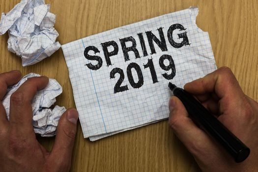 Writing note showing Spring 2019. Business photo showcasing time of year where flowers rise following winter season Man holding marker notebook paper crumpled papers several tries