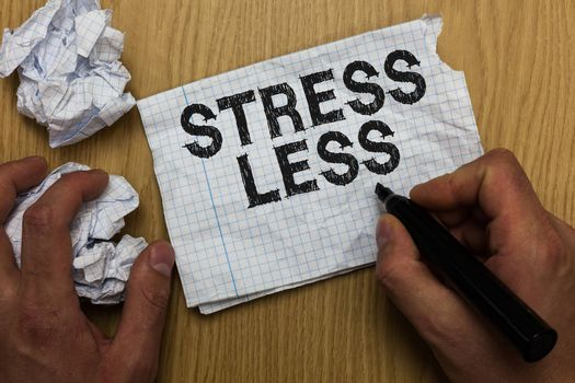 Writing note showing Stress Less. Business photo showcasing Stay away from problems Go out Unwind Meditate Indulge Oneself Man holding marker notebook paper crumpled papers several tries