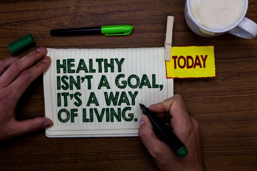 Word writing text Healthy Isn t not A Goal, It s is A Way Of Living.. Business concept for Create good habits routines Man holding marker notebook clothespin reminder wooden table cup coffee