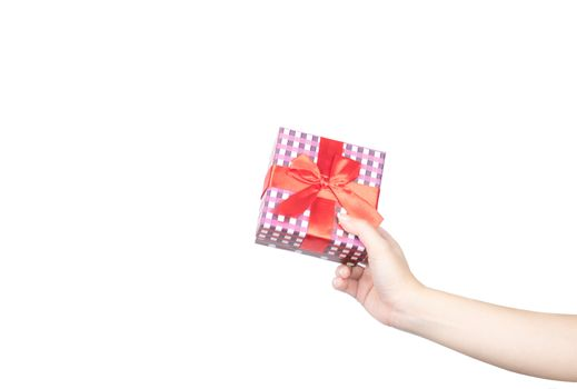Closeup beautiful and healthy woman hands with neat manicure are holding a Christmas gift box wrapped with red ribbon isolated on white background