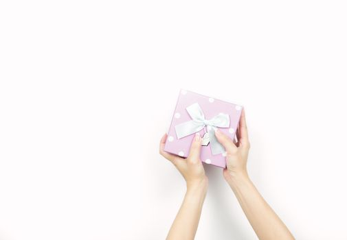 Closeup beautiful and healthy woman hands with neat manicure are holding pink gift box with polka dotted pattern isolated on white background