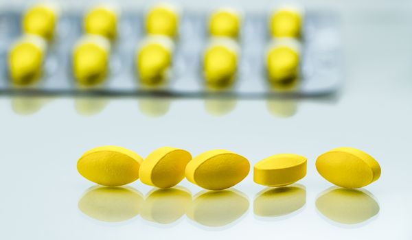 Macro shot detail of yellow oval tablet pills on white background with blister packs as background. Painkiller medicine. Pharmaceutical industry. Pharmacy background.
