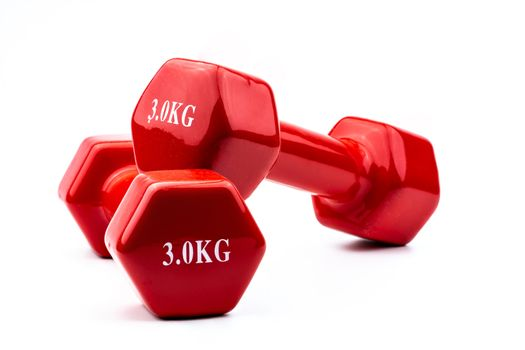 Two red dumbbells isolated on white background with copy space for text. 3.0 kg dumbbell. Weight training equipment. Bodybuilding workout accessories. Healthy lifestyle concept.