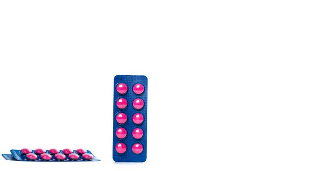 Ibuprofen in pink tablet pills pack in blue blister pack isolated on white background with copy space. Ibuprofen for relief pain, headache, high fever and anti-inflammatory. Painkiller tablets pills.