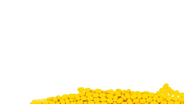 Yellow tablets pills isolated on white background with copy space for text. Ibuprofen tablets pills. Painkiller medicine for headache, high fever and anti inflame. Pharmaceutical industry concept.