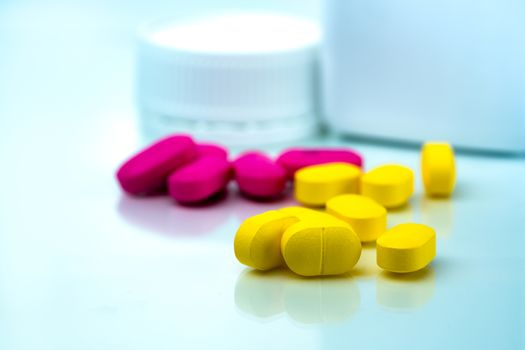 Pile of yellow and pink tablets pills on blurred background of plastic pills bottle with copy space. Ibuprofen for relief pain. Pharmaceutical industry and drugstore concept. Painkiller tablet pills