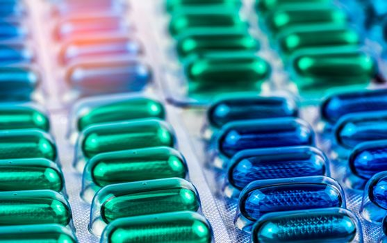 Selective focus on blue and green soft gel capsule pills in blister pack. Naproxen and ibuprofen (Nonsteroidal anti-inflammatory drugs) : Painkiller medicine. Pharmaceutical packaging industry.