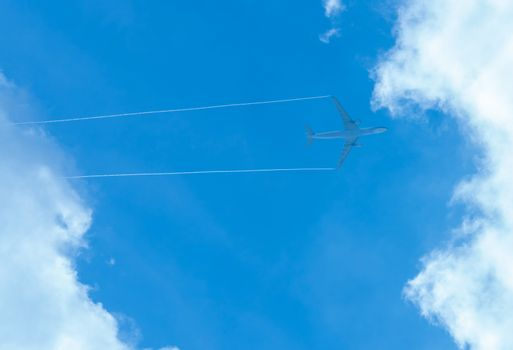 Airplane on blue sky and white clouds. Commercial airline flying on blue sky. Travel flight for vacation. Aviation transport.