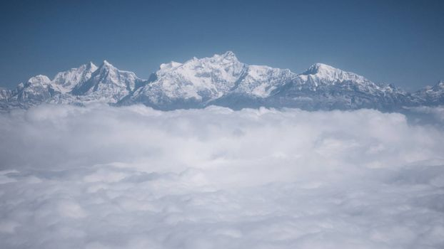The Himalayas as seen from an airplane in Nepal. Layer of clouds beneath the mountain tops.