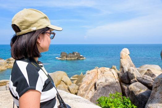 Young woman tourist is standing looking at Hin Ta Hin Yai and beautiful nature landscape of blue sea and sky during summer travel at Koh Samui island, Surat Thani, Thailand