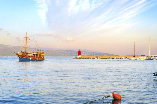 The red lighthouse, mole at Krk town, Croatia, boats docked at the harbour pier and a sail boat entering at sunset. A small cylindrical tower at the biggest port of the island.