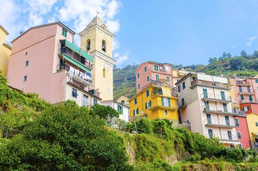 Manarola town, Riomaggiore, La Spezia province, Liguria, northern Italy. View of the colourful houses on surrounding hills and San Lorenzo defence bell tower. Part of the Cinque Terre National Park and a UNESCO World Heritage Site.