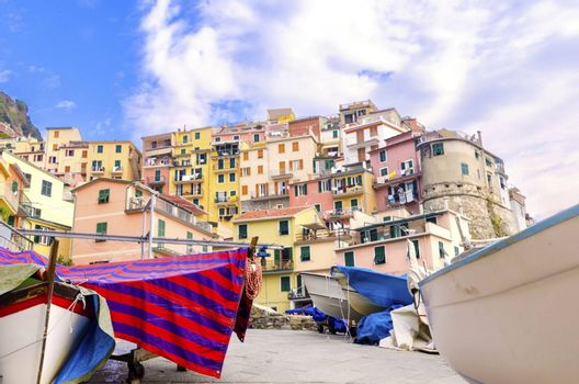 Manarola town, Riomaggiore, La Spezia province, Liguria, northern Italy. View of the colourful houses on surrounding hills, boats balconies and windows. Part of the Cinque Terre National Park and a UNESCO World Heritage Site.