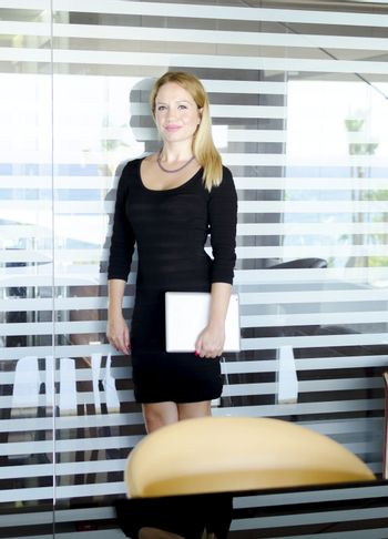 One modern beautiful young blonde white caucasian professional business woman smiling, looking confident, holding a tablet, wearing a tight work office black dress, standing in a conference meeting room alone with big windows on background.