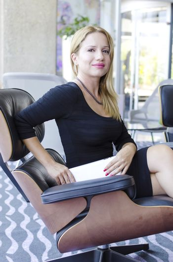 One modern beautiful young blonde white caucasian professional business woman smiling, looking confident, holding a tablet, wearing a tight work office black dress, sitting on a chair in a conference meeting room alone with big windows on background.