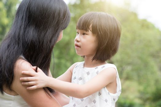 Asian family outdoors portrait. Mother and daughter enjoying at garden park.