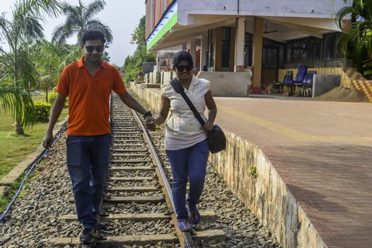 The young couple walking on a railway track. Traveler having fun at railway station holding hands to keep balance. Married couple holding hands walking on the tracks.