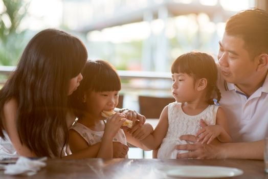 Children eating and sharing bread at cafeteria. Asian family outdoor lifestyle with natural light.