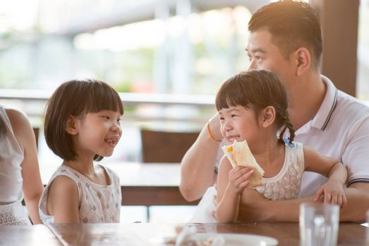 Happy children eating toast bread at cafeteria. Asian family outdoor lifestyle with natural light.