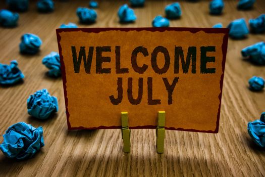 Conceptual hand writing showing Welcome July. Business photo text Calendar Seventh Month 31days Third Quarter New Season Clothespins holding orange paper note crumpled papers mistake