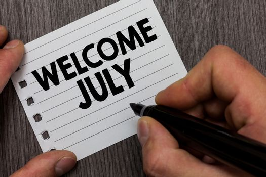 Conceptual hand writing showing Welcome July. Business photo showcasing Calendar Seventh Month 31days Third Quarter New Season Man holding marker notebook page Wooden background