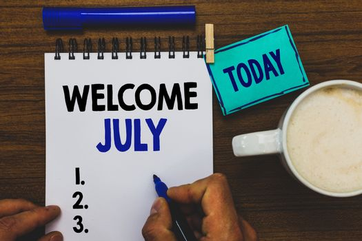 Conceptual hand writing showing Welcome July. Business photo text Calendar Seventh Month 31days Third Quarter New Season Man holding marker notebook clothepin reminder wooden table coffee