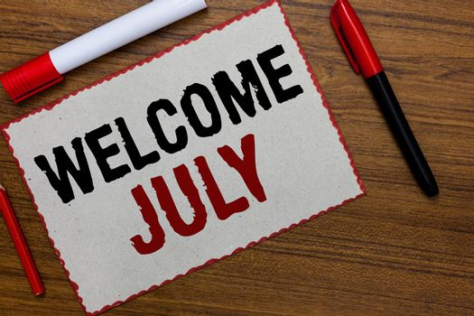 Text sign showing Welcome July. Conceptual photo Calendar Seventh Month 31days Third Quarter New Season White paper red borders markers wooden background communicating ideas