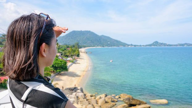 Young woman tourist are looking at the sea and beautiful nature landscape on Lamai beach hight viewpoint during summer travel at Koh Samui island, Surat Thani, Thailand, 16:9 widescreen