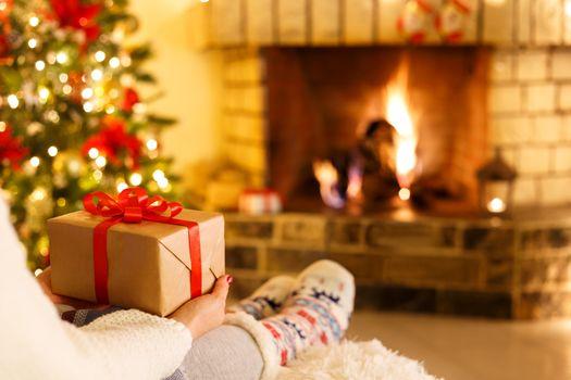 Woman sitting by fireplace