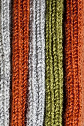 Orange, green and grey wool knitted texture.