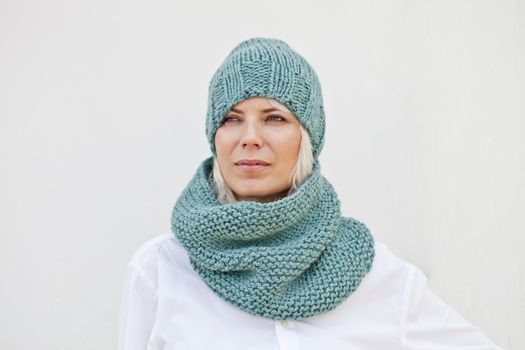 Woman in warm turquoise knitted hat and snood.