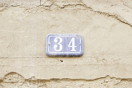 Number thirty-four on the wall of a house, detail of a number of information, even number
