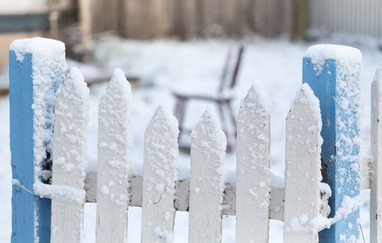 Snow covered picket fence in light falling snow