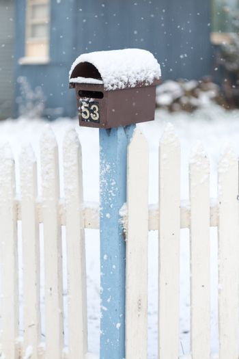 Mailbox and picket fence with falling snow in winter