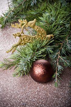 Evergreen fir tree branch, golden deer, brown ball.
