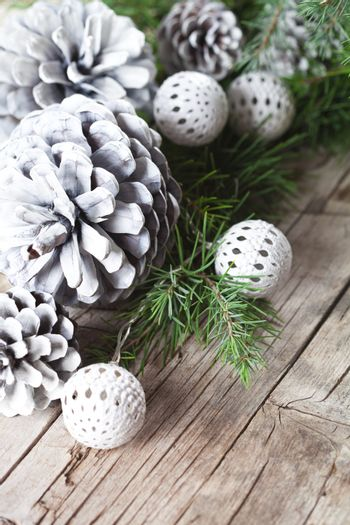 Evergreen fir tree branch, white pine cones and balls.