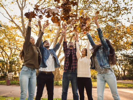 Group of friends in the park having fun throwing leaves in the air
