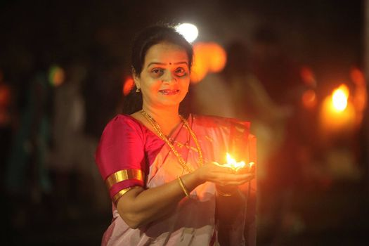 Pune, India - November 2018: A woman lights up a lamp during a public celebration of Diwali festival before sunrise, in India.