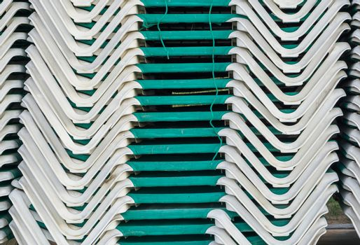 pile of stacked green sunbeds summer season beach lounge background pattern