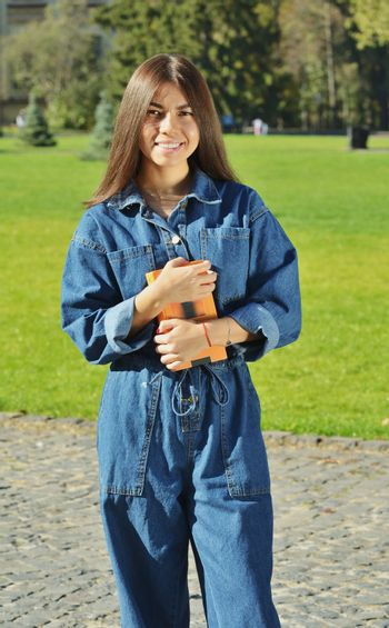 A student in a denim suit stands on the territory of the University