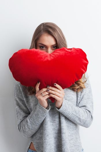 Beautiful woman with red pillow heart, valentine's day concept