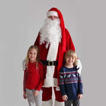 Portrait of Two Children and Santa Claus on gray background