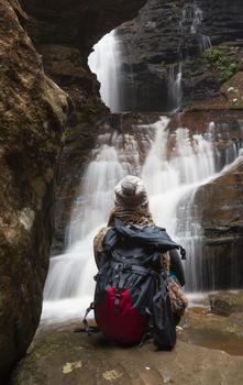 Bushwalker sits in awe of the large waterfalls