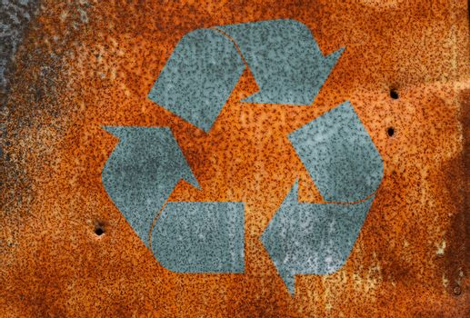 Rust stained corroded metal surfacewith recycling logo sign