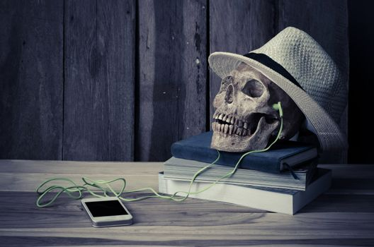 still life - skull have headphone on books and hat on wooden table