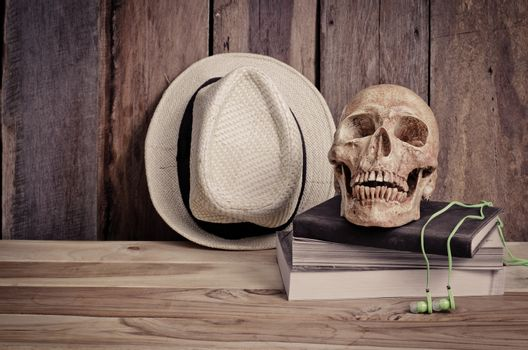 still life - skull on books and hat on wooden table