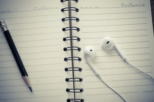 The notebook is turned on and a pencil with headphones