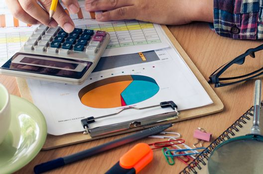 Businessman working on a desk numerical analysis, financial accounting, sales graphs.